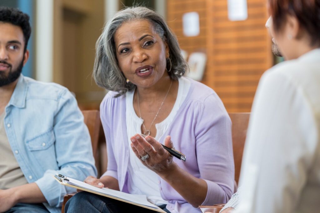 Confident senior African American female therapist discusses something during a support group meeting.