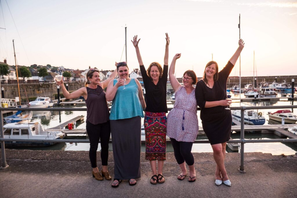 The Onion Collective team of Directors. 5 women standing in a row in a marina.