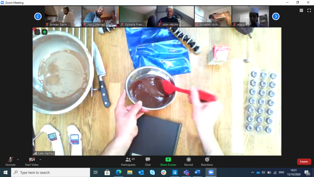 white hands holding a red spoon,  stirring melted chocolate in a bowl