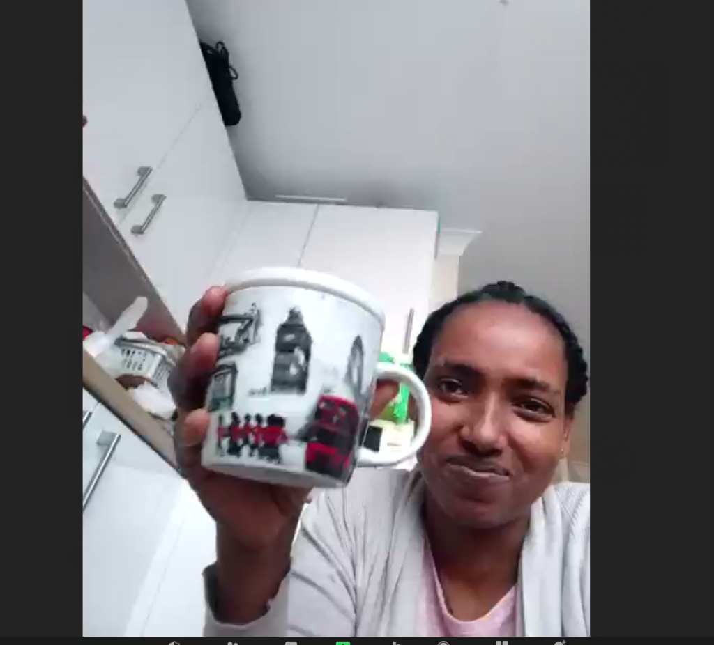 Woman holding a mug up to the screen.,