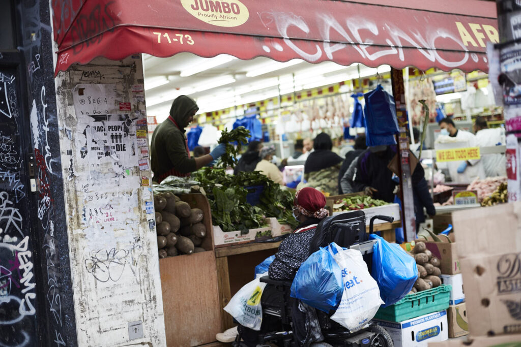 A busy fruit and veg shop entrance, woman in wheelchair, wearing a face mask with lots of shopping bags.