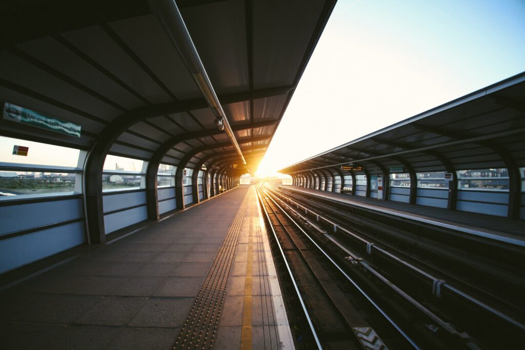 an empty train platform with sun rising in the horizon.