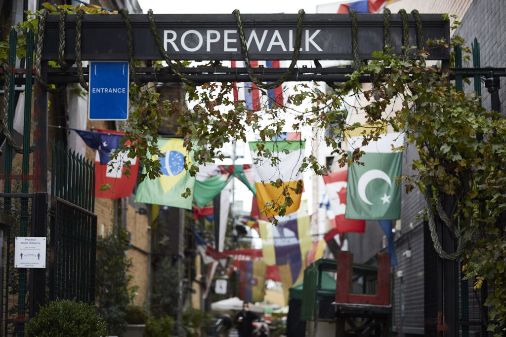 Rope Walk, South London. An ivy covered sign saying Rope Walk, with  lots of international flags hanging behind it.