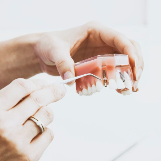 Woman holding dentures and a dental tool