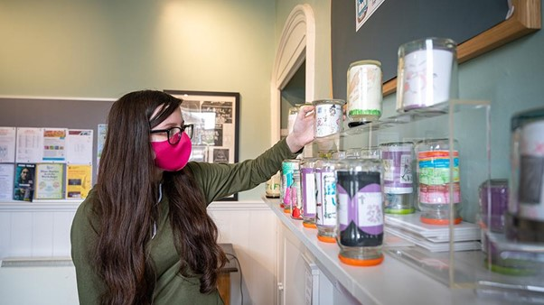 Young person wearing a mask standing in front of a row of jars. Getting work experience curating the 'Museum in a Jar' exhibition