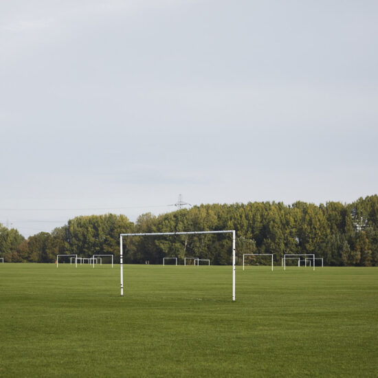 Empty goal in a field with hedgerows in the background
